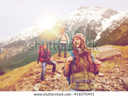 adventure, travel, tourism, hike and people concept - group of smiling friends with backpacks walking down downhill over alpine mountains and hills background - stock photo