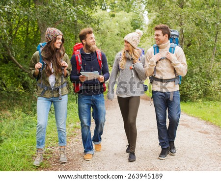 adventure, travel, tourism, hike and people concept - group of smiling friends with backpacks and map walking outdoors - stock photo
