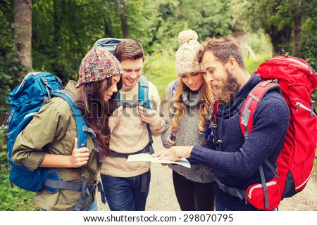 adventure, travel, tourism, hike and people concept - group of smiling friends with backpacks and map outdoors - stock photo