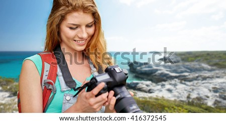adventure, travel, tourism, hike and people concept - happy young woman with backpack and camera photographing over seashore or beach background - stock photo