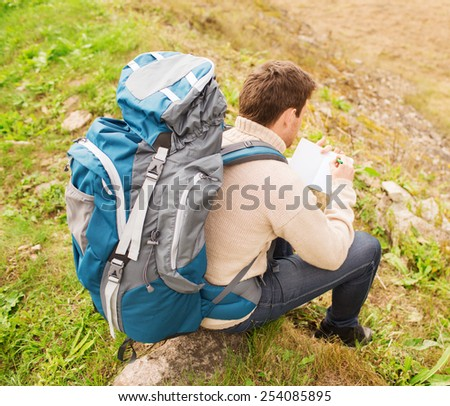 adventure, travel, tourism, hike and people concept - man with backpack sitting on ground from back - stock photo