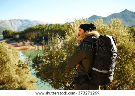 Adventure, travel, tourism, hike and people concept - man with beard and black backpack hiking. Hiker - man hiking in forest. Male hiker looking to the side walking in forest. Man outdoors in nature.