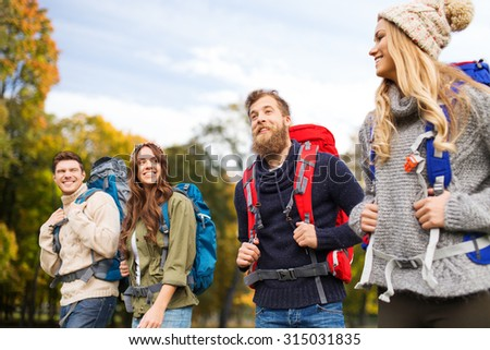 adventure, travel, tourism, hike and people concept - smiling friends walking with backpacks over natural background - stock photo