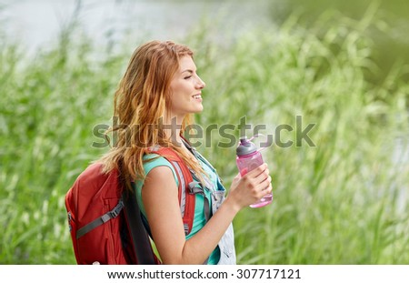 adventure, travel, tourism, hike and people concept - smiling young woman with backpack and bottle of water outdoors - stock photo