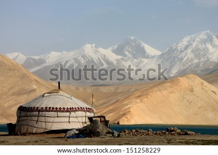 Adventure Travels Pamir Karakorum Highway Mushtaq Ata Peak at Karakul Lake - stock photo