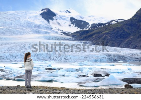 Adventure woman by glacier nature on Iceland. Tourist in Icelandic sweater by glacial lagoon / lake of Fjallsarlon, Vatna glacier, Vatnajokull National Park. Young woman visiting nature landscape. - stock photo
