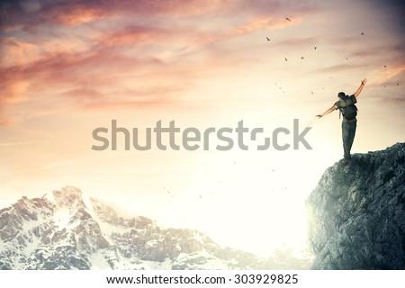 Adventurer climber reach the top of the mountain - stock photo
