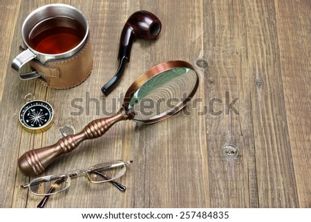 Adventures Or Travel Or Expedition Items On Wooden Table. Tea Mug, Vintage Magnifying Glass, Compass, Smoking Pipe, Glasses - stock photo