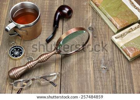 Adventures Or Travel Or Expedition Items On Wooden Table. Tea Mug, Vintage Magnifying Glass, Compass, Two Retro Notebooks, Smoking Pipe, Glasses - stock photo