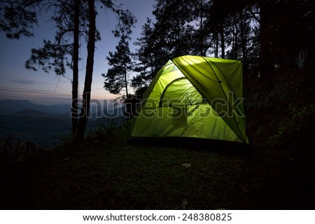 Adventures with green tent in the forest on the hills. - stock photo