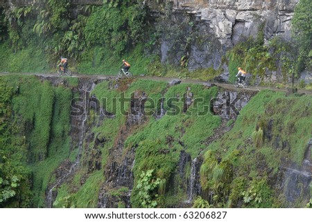 Adventurous bikers riding along the narrow road of death, North Yungas Road, northeast of La Paz, Bolivia - stock photo