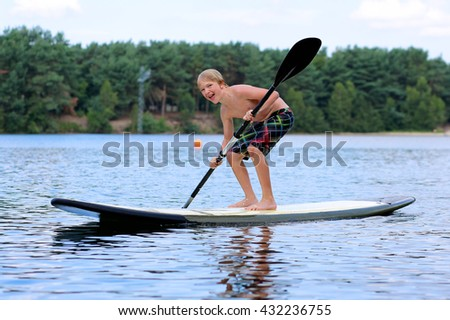 Adventurous boy learning to paddle on stand up board. Happy child, teenage schoolboy, having fun enjoying adventurous experience on the river on a sunny day during summer holidays - stock photo