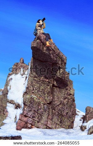 Adventurous female photographer is sitting on a rock pinnacle while shooting. Travel, adventure, active recreation concept. - stock photo