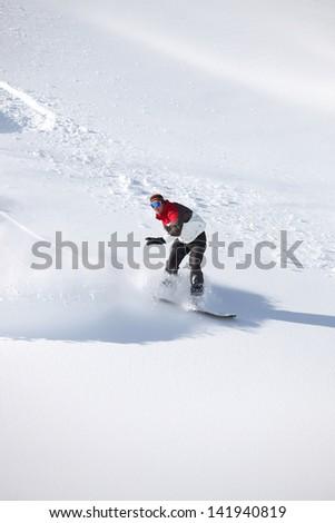 Adventurous man snowboarding down hill - stock photo
