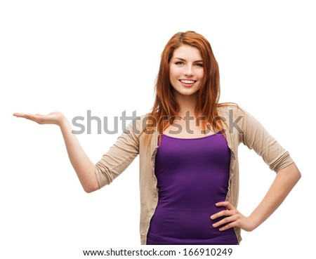 advertisement concept - attractive teenager in casual clothes holding something on the palm of her hand - stock photo