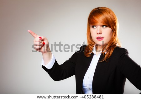 Advertisement concept - redhead business woman pointing with finger showing blank copy space on gray background - stock photo