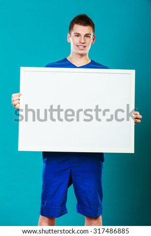 Advertisement concept. Young man holding blank presentation board. Male model showing banner sign billboard copy space for text on blue - stock photo