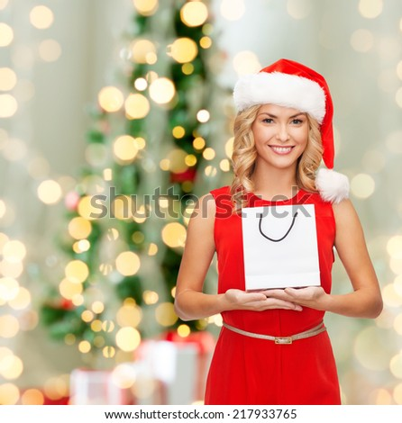 advertisement, holydays and sale concept - smiling woman in santa helper hat with white blank shopping bag over living room with christmas tree background - stock photo
