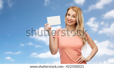 advertisement, invitation, message and people concept - smiling young woman or teenage girl with blank white paper card over blue sky and clouds background - stock photo