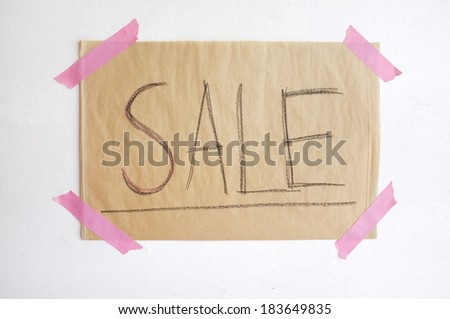 advertisement sale brown paper on white wall - stock photo