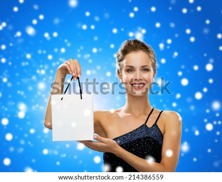 advertisement, winter holidays, christmas and sale concept - smiling woman with white blank shopping bag over black background over blue snowy background - stock photo