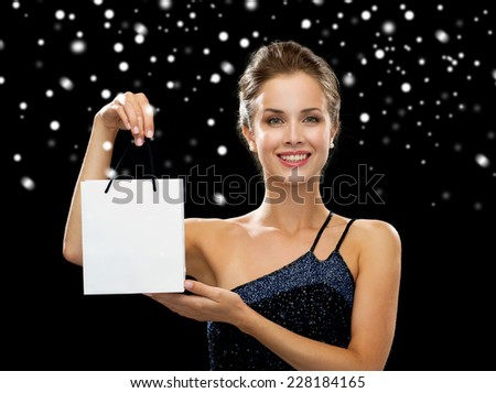 advertisement, winter holidays, christmas and sale concept - smiling woman with white blank shopping bag over black background over black snowy background - stock photo