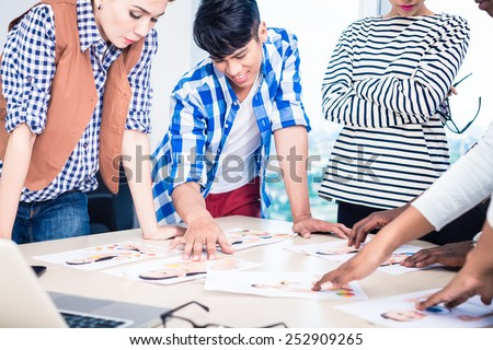 Advertising agency team choosing model for campaign among pictures spread out on table - stock photo