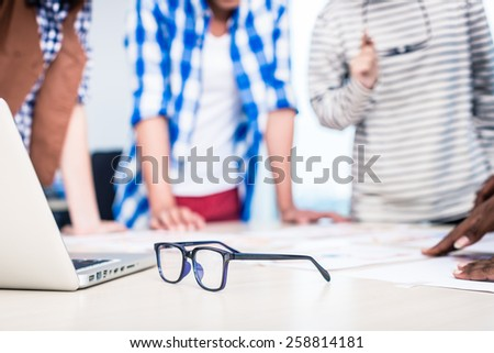Advertising agency team in creative meeting, focus on glasses in foreground - stock photo