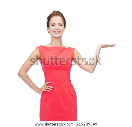 advertising and happy people concept - smiling woman in red dress holding something imaginary on palm of her hand - stock photo