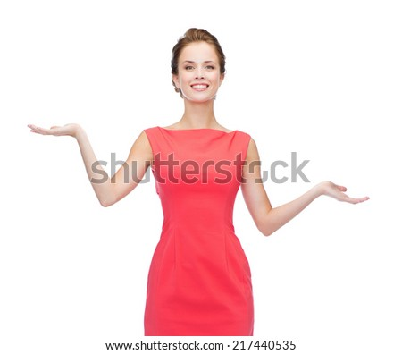 advertising and happy people concept - smiling woman in red dress holding something imaginary on palms of her hands - stock photo