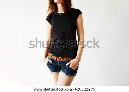 Advertising and T-shirt design concept. Close up of black copy space T-shirt on stylish teenager model posing with hands in pockets of trendy denim shorts isolated against white copy space studio wall - stock photo