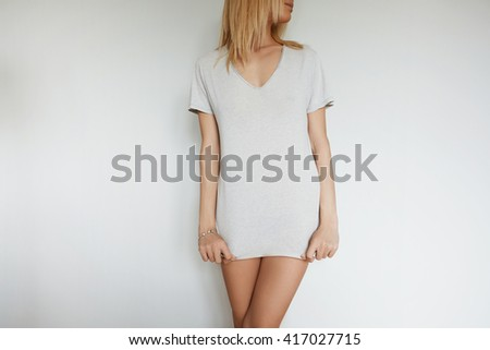 Advertising and T-shirt design concept: cropped portrait of attractive young female model with blond hair posing in gray blank copy space T-shirt for your promotional content against white studio wall - stock photo