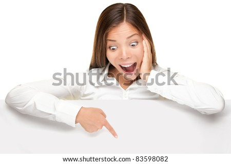 advertising banner sign - woman excited pointing looking down on empty blank billboard paper sign board. Young business woman isolated on white background. - stock photo