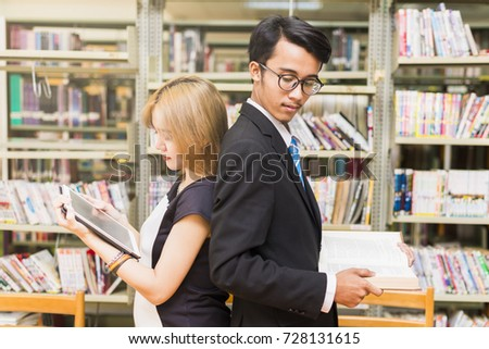 Advertising,Business Concept -Inquisitive Asian businessman looking at Tablet screen of businesswoman trying to steal idea of competitor, copying work at corporate exam, gathering information on rival