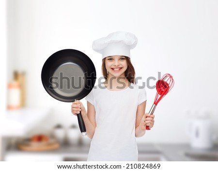 advertising, childhood, cooking and people - smiling girl in white t-shirt and cooking hat holding pan over blue background