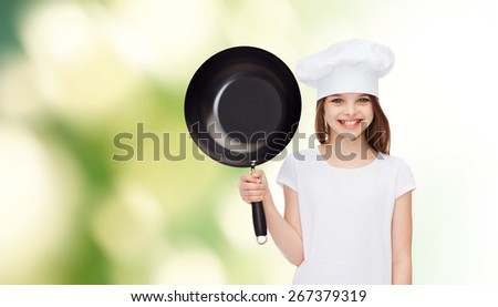 advertising, childhood, cooking and people - smiling girl in white t-shirt and cooking hat holding pan over green background - stock photo