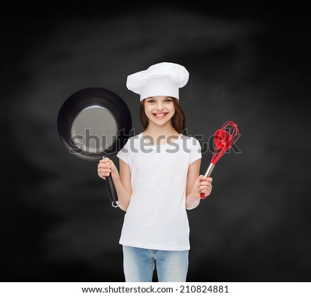 advertising, childhood, cooking, education and people - smiling girl in white t-shirt and cooking hat holding pan over blackboard background - stock photo