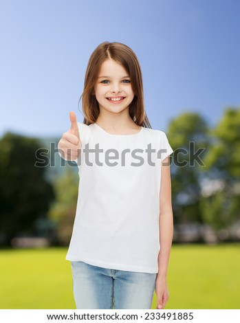 advertising, childhood, nature and people - smiling little girl in white blank t-shirt showing thumbs up gesture over green park background - stock photo