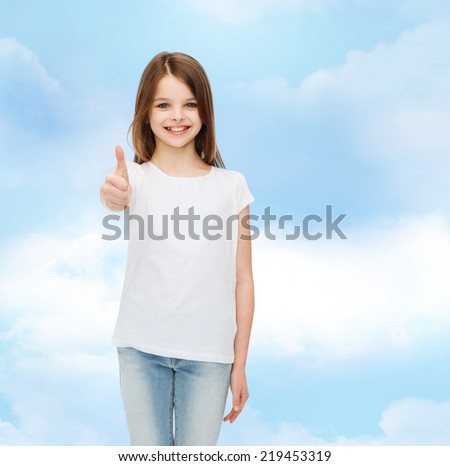 advertising, dream, childhood, gesture and people - smiling little girl in white blank t-shirt showing thumbs up over cloudy sky background - stock photo