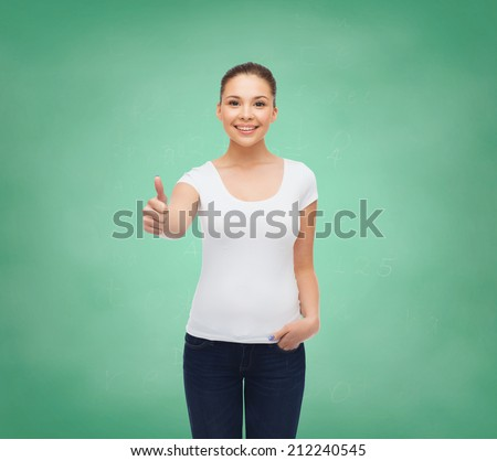 advertising, education, school, gesture and people concept - smiling young woman in blank white t-shirt showing thumbs up over green board background - stock photo
