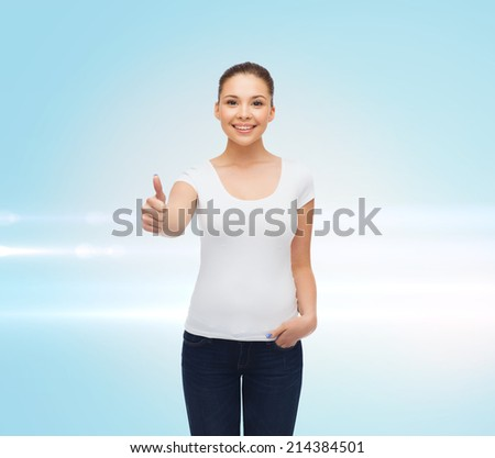 advertising, gesture and people concept - smiling young woman in blank white t-shirt showing thumbs up over blue laser background - stock photo