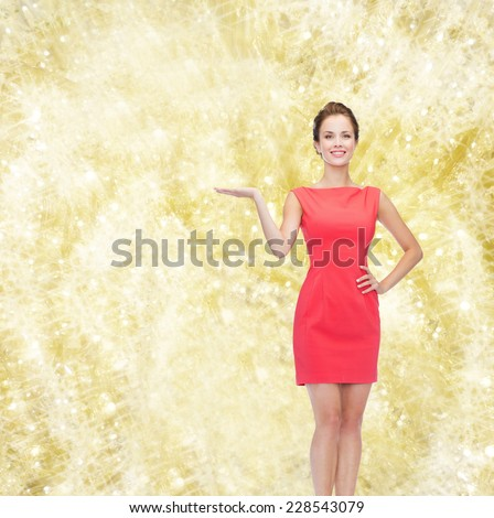 advertising, holidays and people concept - smiling young woman in red dress holding something on palm of her hand over yellow lights background - stock photo