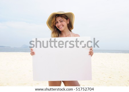 Advertising on the beach: woman showing blank board with copy space for your ad