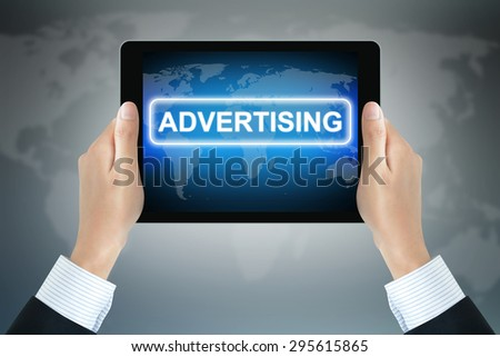 ADVERTISING sign on tablet pc screen held by businessman hands - stock photo