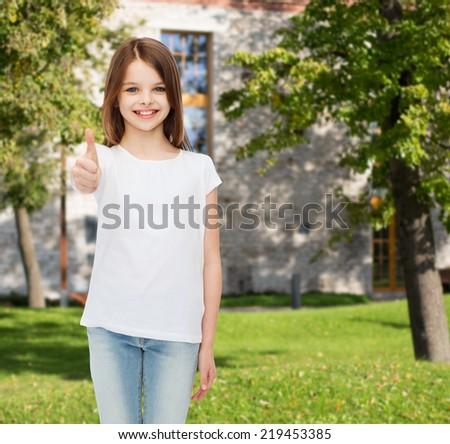 advertising, summer vacation, gesture, childhood and people - smiling little girl in white t-shirt showing thumbs up over campus background - stock photo