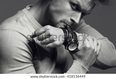 Advertising wrist watch concept. Beautiful (handsome) muscular male model with perfect body in grey jumper. He bites and unfastens the bracelet from the clock. Street style. monochrome studio shot - stock photo