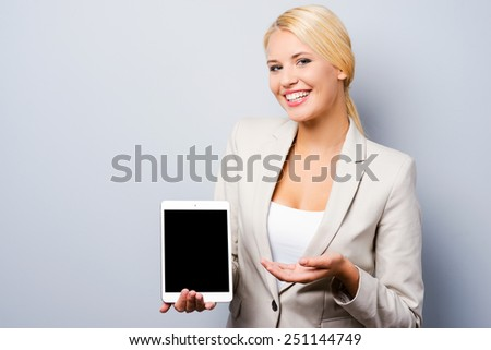 Advertising your product. Beautiful young businesswoman showing her digital tablet while standing against grey background - stock photo