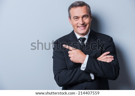 Advertising your product. Cheerful mature man in formalwear looking at camera and smiling while pointing away and standing against grey background - stock photo