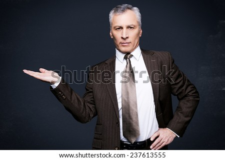 Advertising your product. Confident senior man in formalwear looking at camera and holding copy space in his hand while standing against blackboard - stock photo
