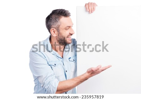 Advertising your product. Happy young man in casual wear leaning at copy space and pointing it while standing against white background - stock photo